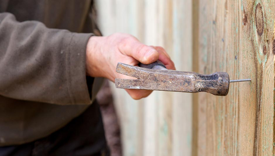 person building a timber fence