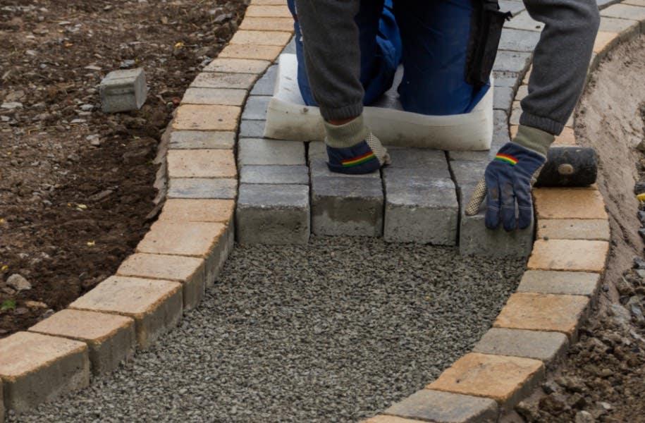 Man kneeling on ground laying some paving