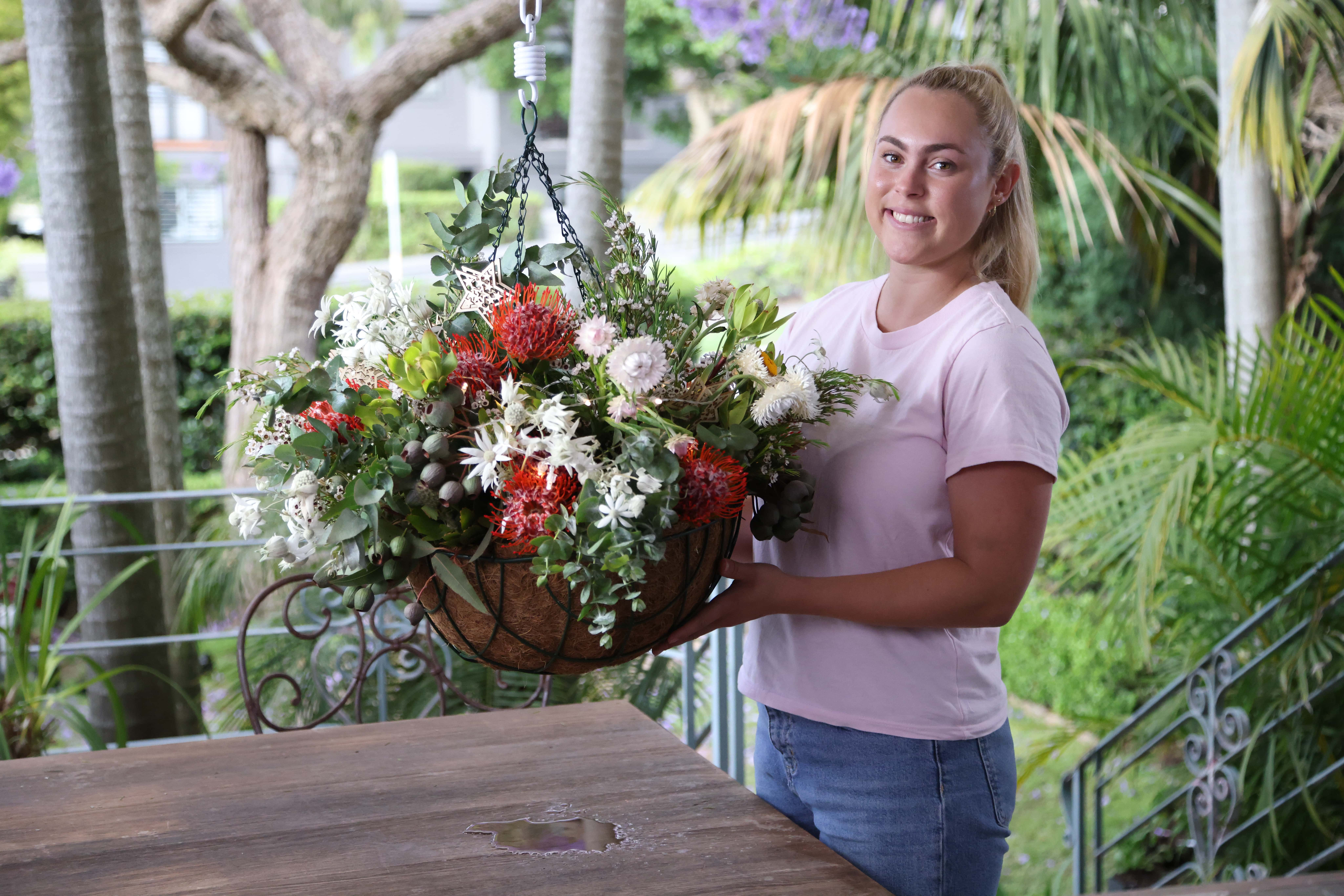 a woman carrying a festive hanging basket