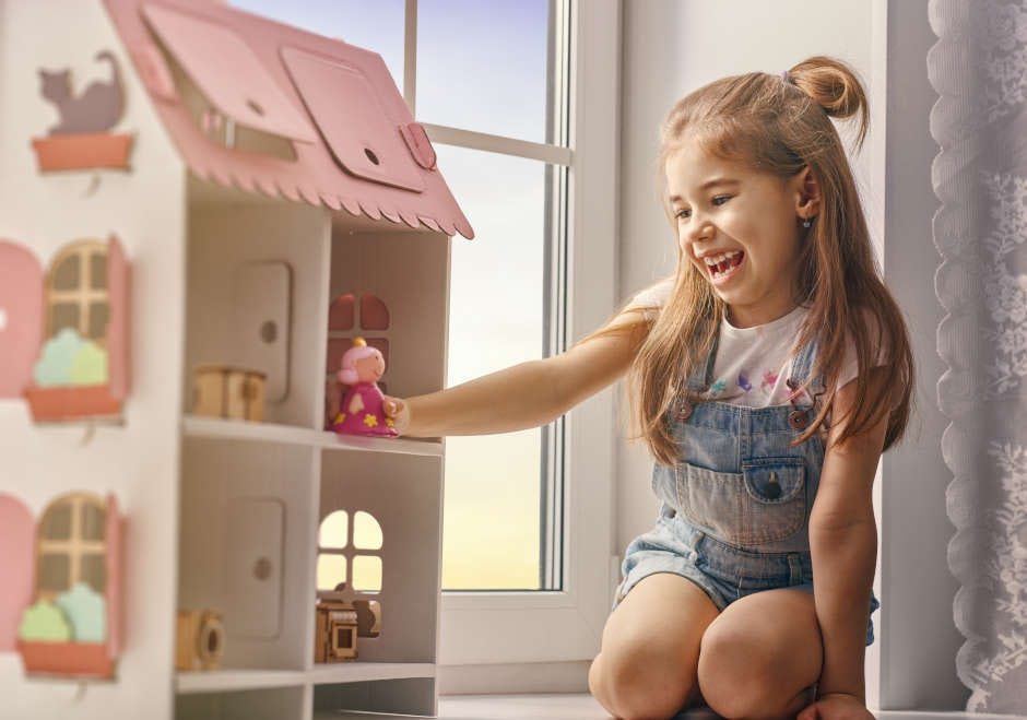 girl playing with a home-built dolls house