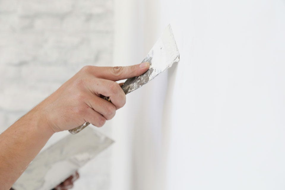 person patching a hole in a plaster wall