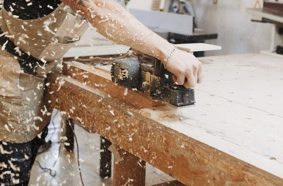 man using planer on wooden workbench