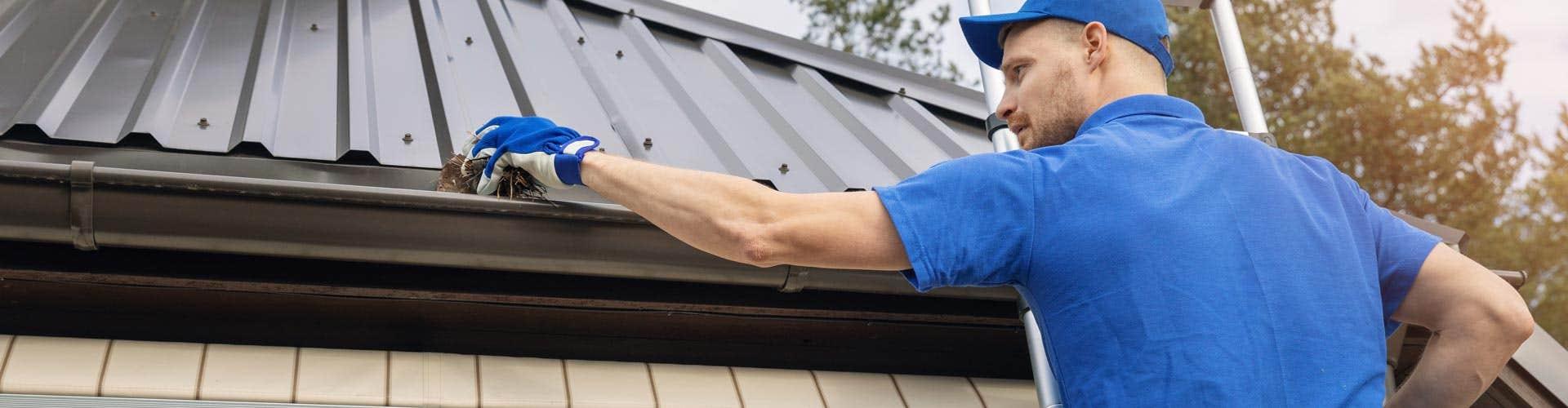 man cleaning a home gutter