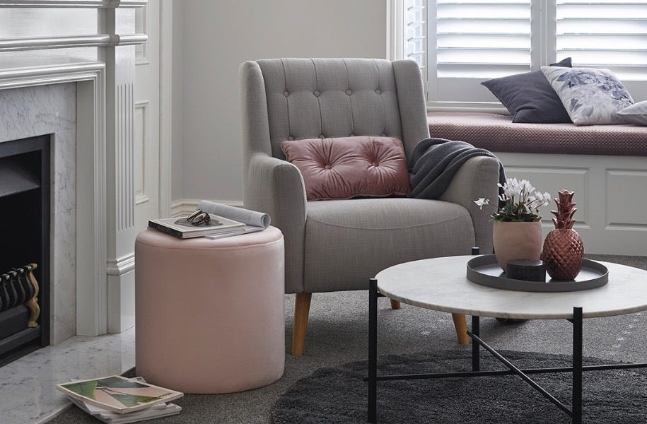lounge room with coffee table, pink ottoman and grey chair