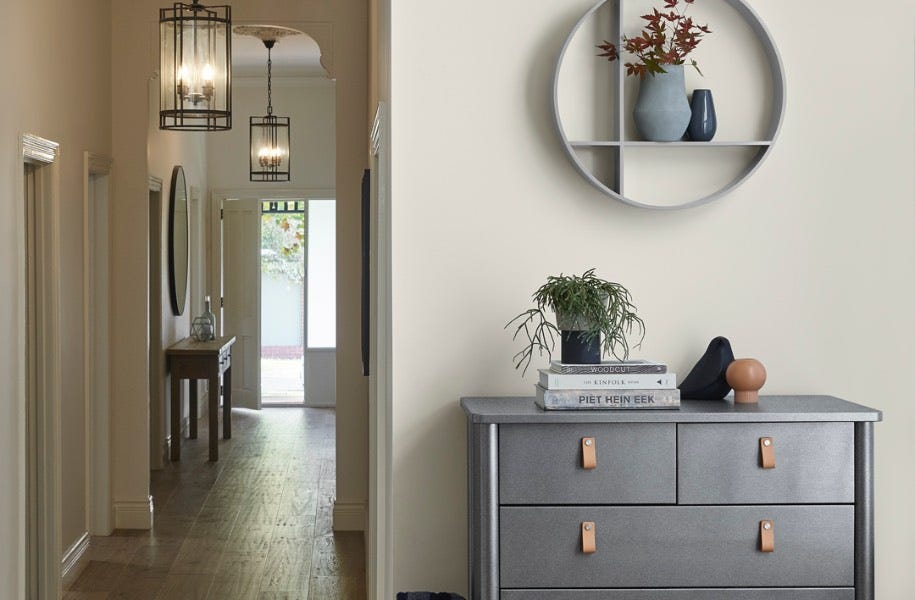 Hallway with pendant lights, chest of drawers and round shelving